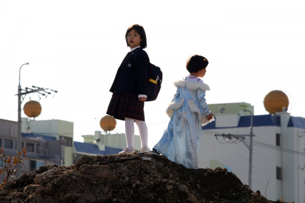 Two Korean children standing on a hill