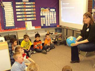 Teacher holding a globe in front of a classroom of small children.